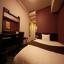 落ち着いたデザインのコンフォートシングルルーム。お部屋にはズボンプレッサーも常備しております。