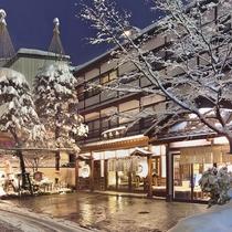 【外観/冬】冬季期間は雪吊りされた玄関前が風物詩に。雪と湯けむり香る冬の情景。