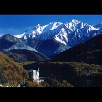 秋の紅葉の北アルプスと山のホテル