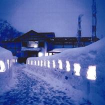 *【冬の外観】幻想的な雪灯籠を通って宿へ。雪深いこの時期だけの美しい光景です。