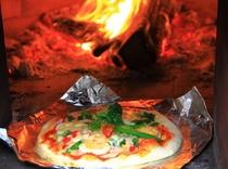 民宿隣の畑で採れたて野菜に使い、自家製ピザ窯で焼きます