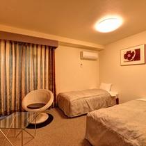 *洋室ツインB(客室一例)/シックでモダンな客室。ラウンドチェアに腰かけて寛ぎのひと時を。
