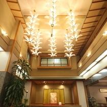 【フロント ロビー】吹き抜けには花をモチーフにした華やかな照明がお客様の到着を歓迎しております。