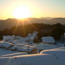 窓から望む朝日と町並み