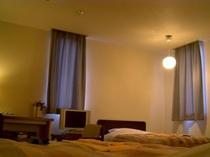 落ち着いた雰囲気のツインルーム。TVは液晶でLAN無料利用意可能。
