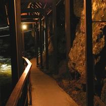 *【渡り廊下】自噴巌風呂へはこちらから…。裸電球の明かりが優しく川沿いの廊下を燈します。