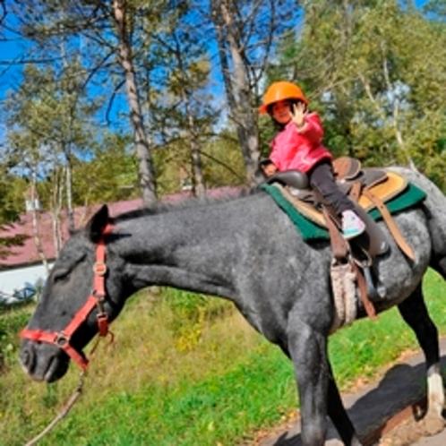 【アクティビティ】乗馬体験=ひとりでできるもん!=初めてのお馬さんにまたがって初乗馬の女の子、すごい