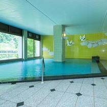 【「丹頂の湯」男性風呂2F】大きな窓の湯けむりの向こうに、大自然の眺望がお楽しみいただける大浴場。