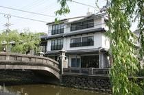 川沿いに本館を眺む