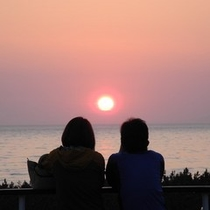 夕陽を眺めるカップル