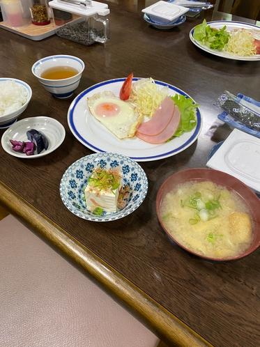 朝食例 ハムエッグ、納豆、小鉢、海苔など