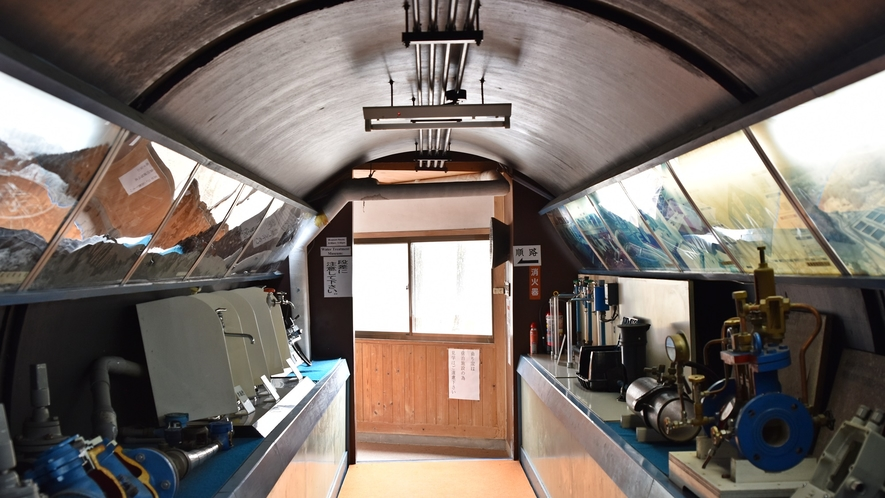 *【客室/曲がり家】曲がり家に続く廊下。昔は水道管として利用、現在は水道工事関わる道具が展示中。