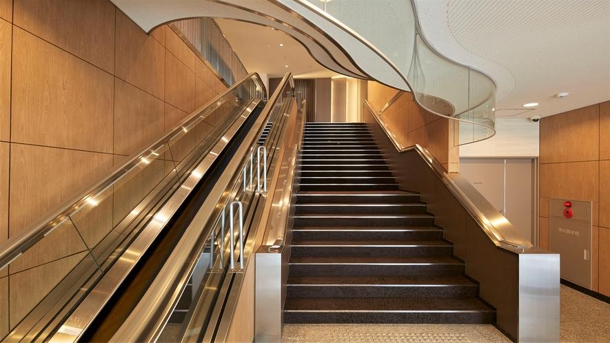 【1F階段・エスカレーター】 フロントは2Fでございます。