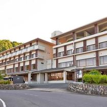 湖を前景に雄大な山々と森の包まれて佇むホテル