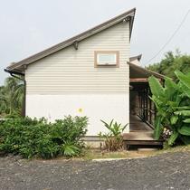*[入口]南国らしい植物にかこまれた建物がフロントへの入口。奥へどうぞ。