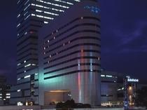 駅西口「そごうデパート」方面からの夜のホテル外観イメージ。上部に青く光るホテル名が目印です。