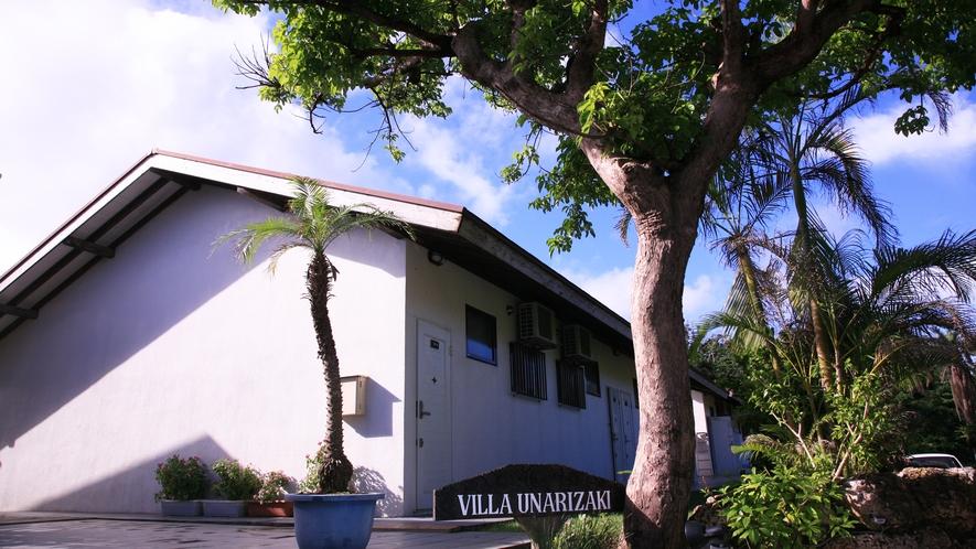*【施設入口】木々のトンネルを抜けると見える、白壁の建物「ヴィラうなりざき」。