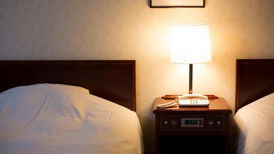 【洋室】ナイトスタンドランプが優しい光を灯します。都会の喧騒や日常を忘れてゆっくりとお休みください。