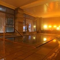 江戸城の修築にも使われた「伊豆石」を使った湯船の大浴場。質感、色等が落ち着く雰囲気です。浴槽から溢れ