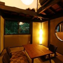 丸窓が特徴的な和室はシックな古民家風