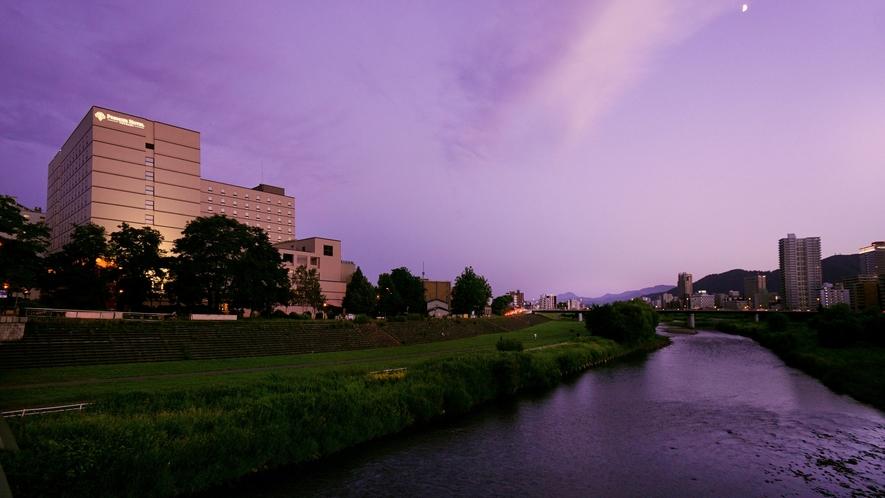 夕方の特別な時間に薄紫色に染まるホテル外観