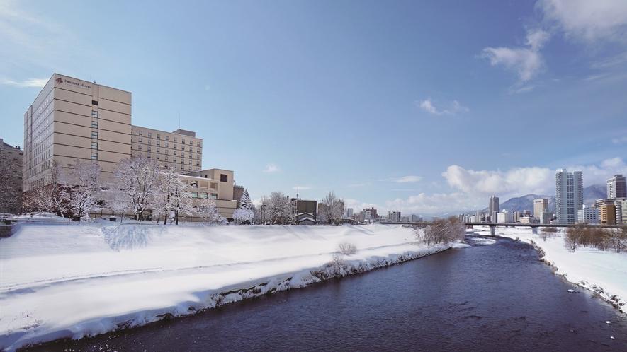 雪に包まれた豊平川に面したホテル外観