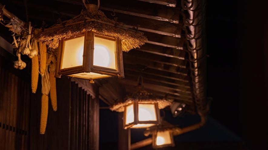 *外観(夜)/建物を照らす明かりも茅の帽子をかぶっています
