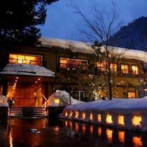 【冬】深い雪が降り積もる米沢の冬。雪の中、オレンジの温かな灯りのともる宿は幻想的な雰囲気が漂う