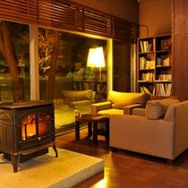 【ラウンジ/夜】降り積もる雪と温かな暖炉の灯り。ここでは日常の喧騒から離れた穏やかな時間が流れる