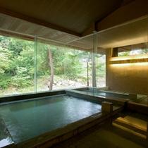 【露天風呂付き大浴場 時と光の湯】渓流に面した大窓からは、四季折々の変わりゆく自然を楽しめる