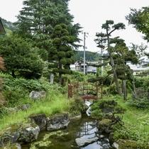 【良実の湯/露天風呂からの眺め】野趣あふれる岩造りの露天風呂から庭を眺める