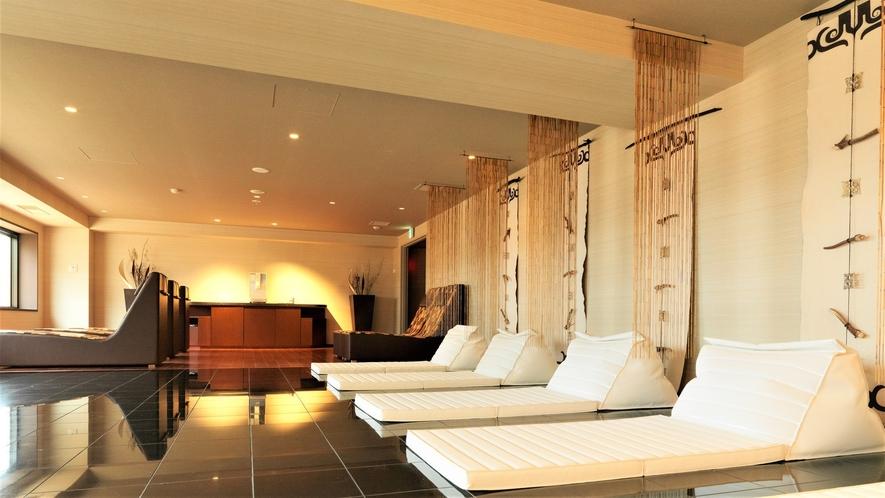 【3F岩盤スパ スマ】岩盤リビング[ニカオプ]/石の寝椅子は床暖ヒーターでほんのり温かい。