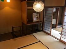2階共有スペースの様子。アジア風の明かりの下、京都の本やリーフレットなどがございます。