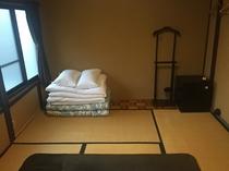 床の間の和室 綺麗にまとめられた布団と備品類。