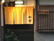 夜の玄関の様子。暖色の明かりが暖簾を優しく照らし、皆様をお迎えします。