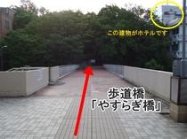 ③ 歩道橋「やすらぎ橋」を渡ります。右前方の、とんがりがある建物が当館です