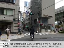 大きな横断歩道を渡ると先に交番がありますので、直進します。大きな道路です。気を付けて横断して下さい。