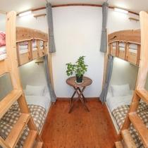 男女混合ドミトリー。オリジナルの木製ベッドでリラックス。