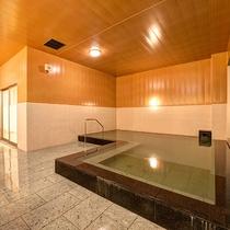*【1階大浴場】落ち着きのある木目と石の浴槽で、ゆったりとお過ごしください。