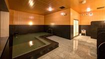 *【1階大浴場】落ち着きのある木目と石の浴槽。ゆったりとお過ごしください。