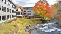 紅葉する阿寒川とホテル外観