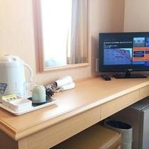デスク(シングルルーム)デスク上備品:テレビ、玄米茶、コップ、湯呑み、ドライヤー