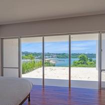 【寝室】主賓室の大きな窓越しに広がる青い海