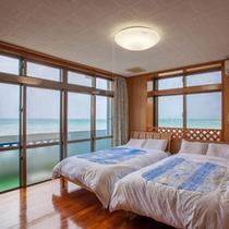 ツインベッドの主賓室からも美しい海が望めます。窓の外は屋嘉ビーチ。