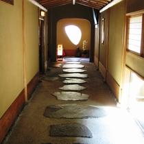 石畳の廊下の先には、半月窓から庭園が望めます