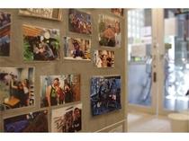 【思い出アルバム】フロント周辺の壁面にはゲストとの思い出の写真がずらりと並びます。