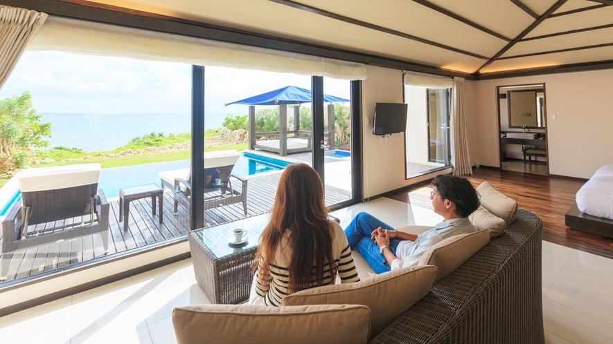 *【客室】広々としたリビングのソファからはテラスとプール・宮古島の海がご覧いただけます。