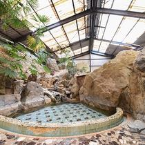 *[岩風呂(夏季季節営業)]大きい岩に囲まれた扇型の浴槽です。