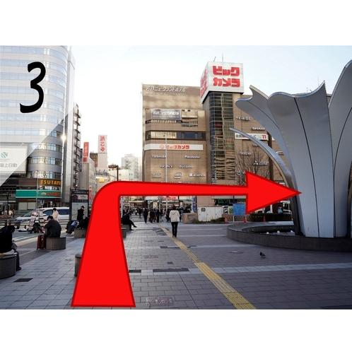 ③正面に家電量販店、手前に信号交差点がありますので、渡って右折します。