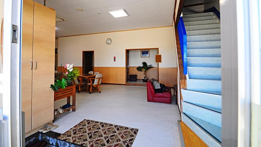【玄関】左に食堂、奥にはくつろげるソファがあり、右の階段でお部屋へ行けます。